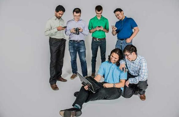 Group of students working on various phones, computers, tablets.